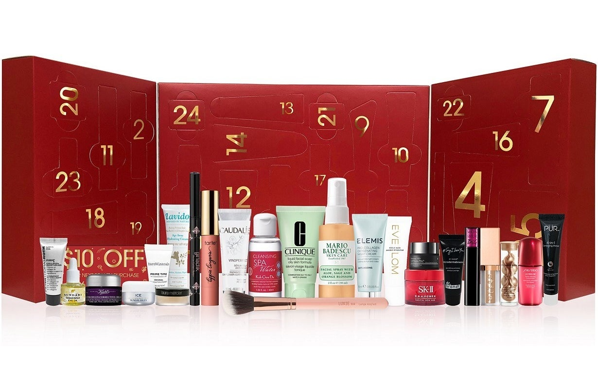 an opened red advent calendar with 24 windows to open filled with mini beauty products