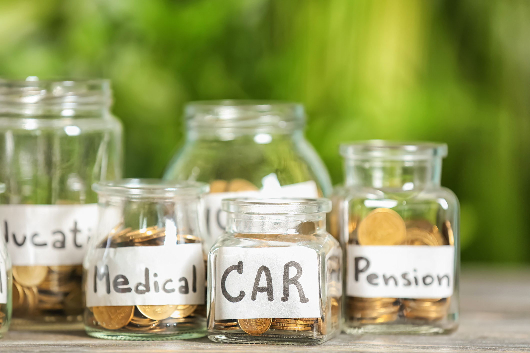 """Jars labeled """"car,"""" """"medical,"""" and """"pension"""" with coins inside"""