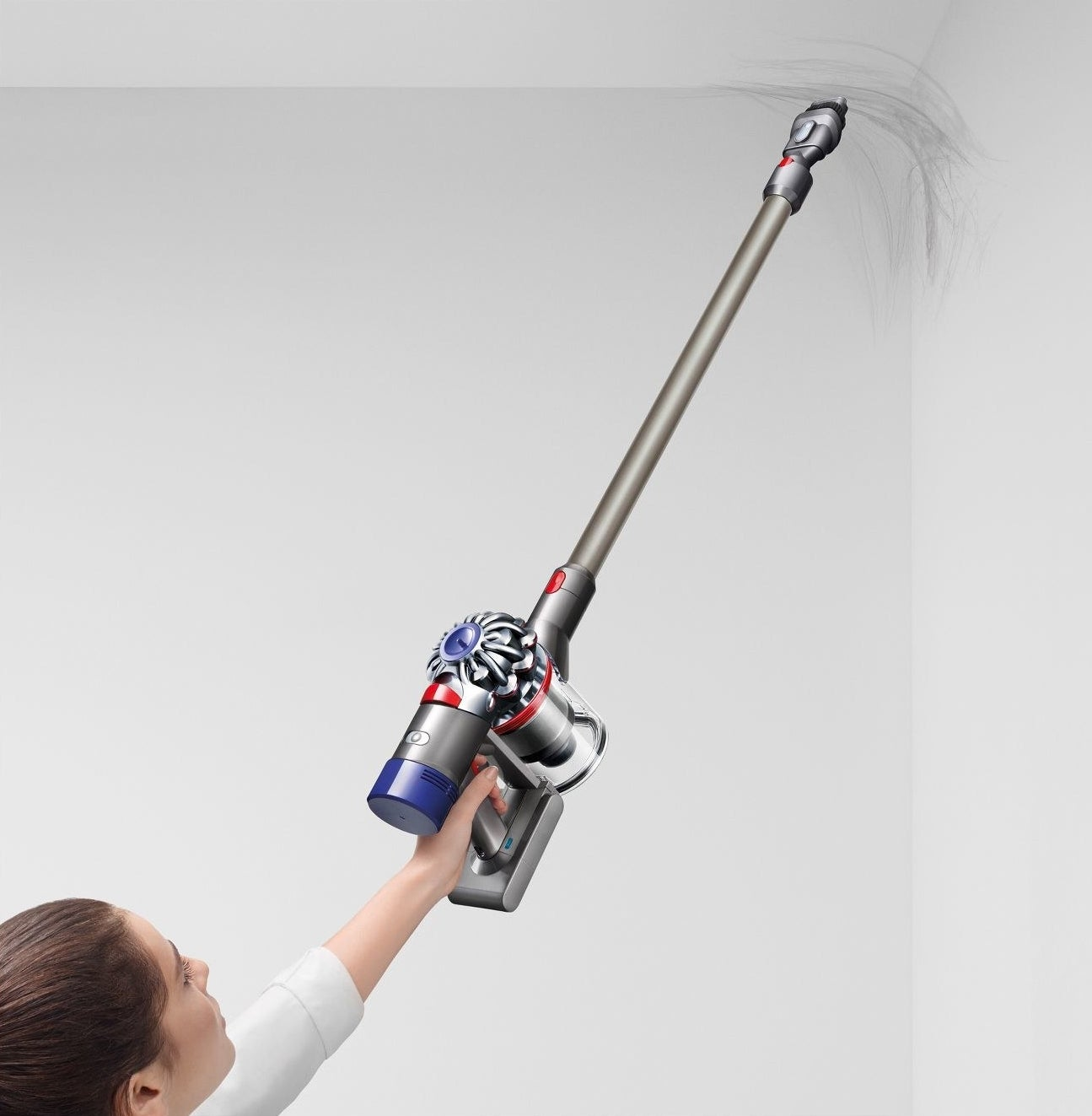 person using cordless dyson vacuum to clean up a cobweb on the ceiling