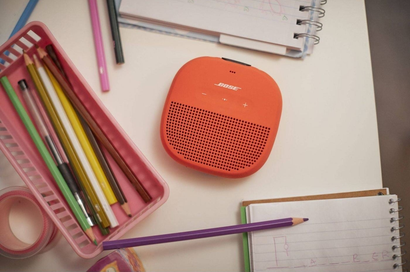 orange Bose bluetooth speaker sitting on a desk