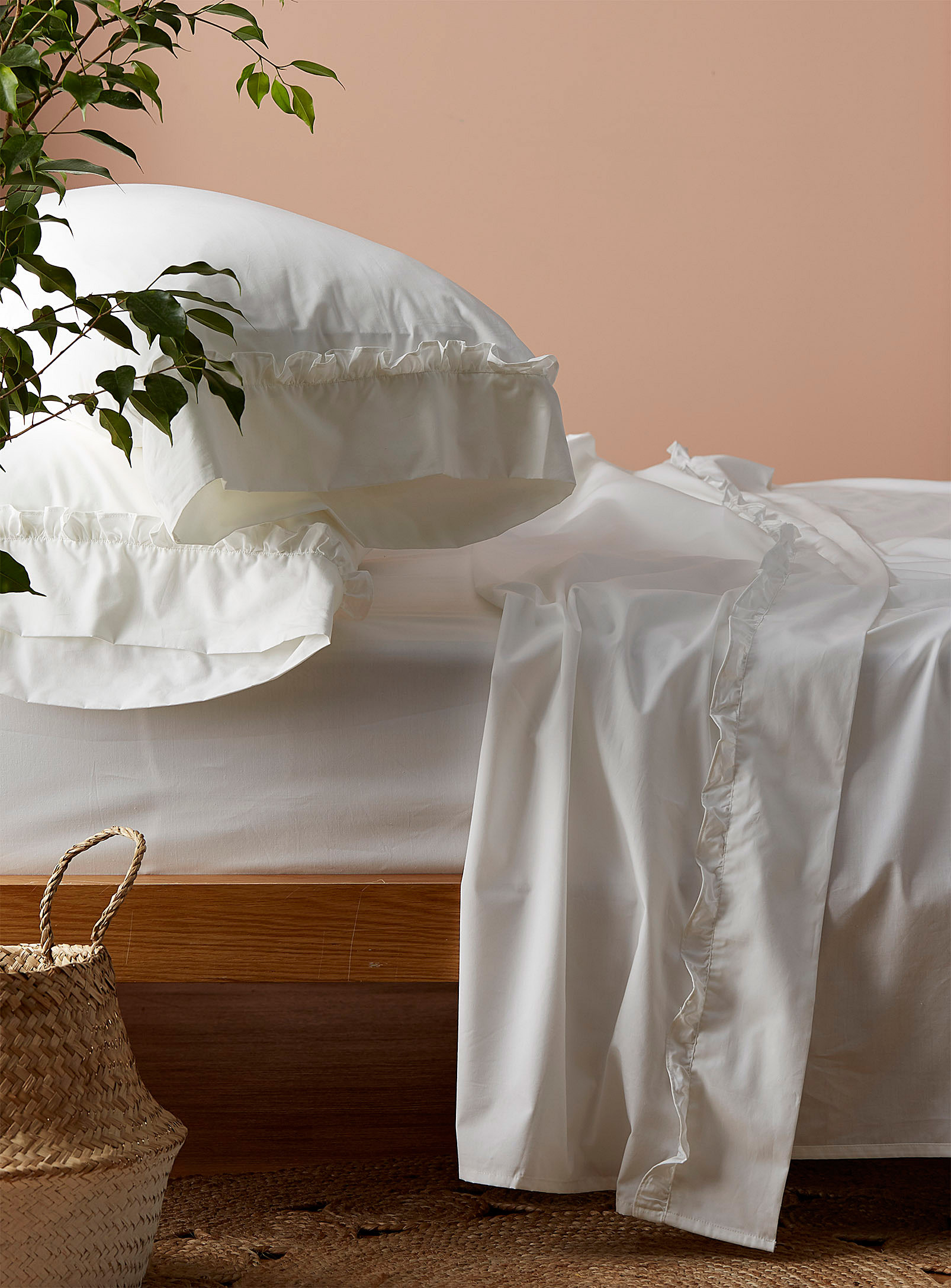A bed neatly made with plain sheets that have a ruffled trim at the top