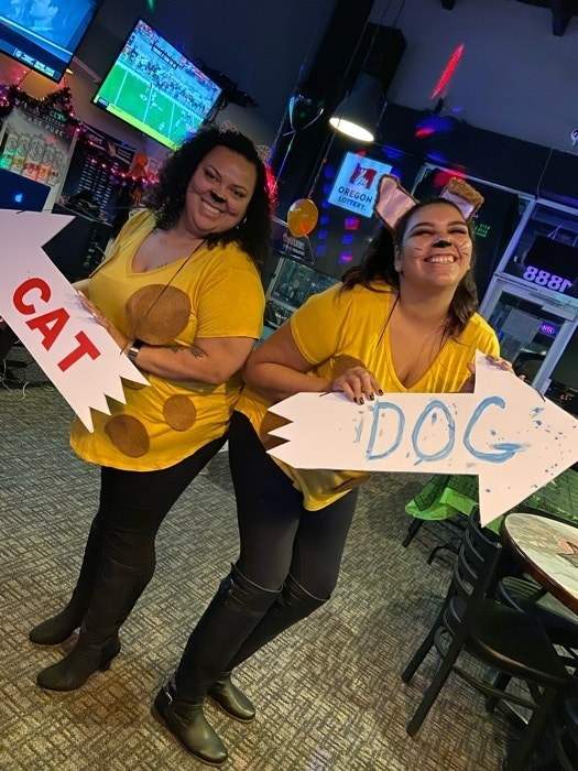 "Two people, adjoined at the hip, dressed in yellow shirts with brown spots, holding signs that read ""Cat"" and ""Dog"""