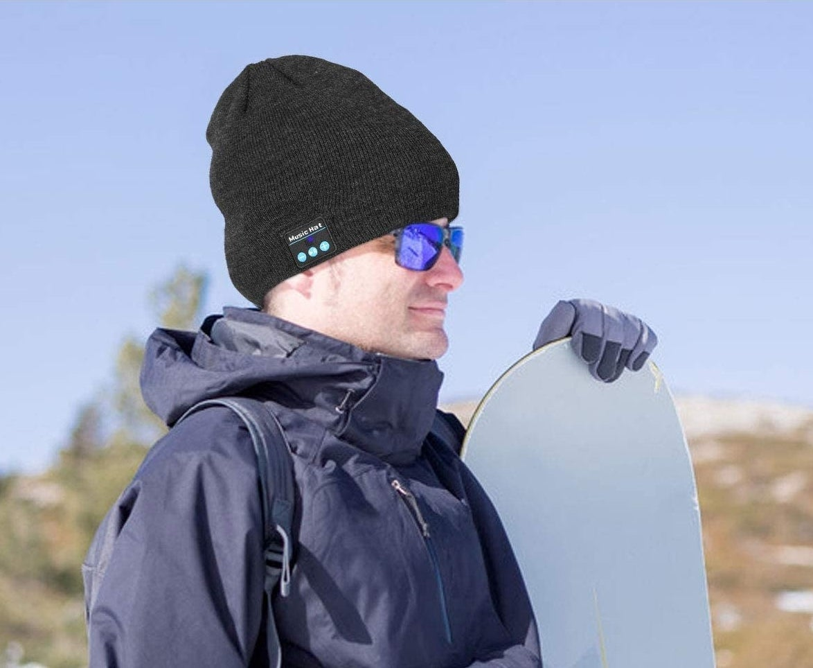 A smiling person wears the toque while preparing to snowboard