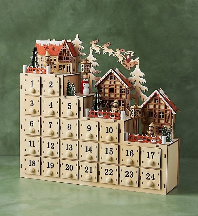 a wooden advent calendar with individual drawers and with a little holiday villager on top
