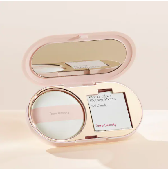 The compact is open on a simple background, showing the pouf and blotting sheets