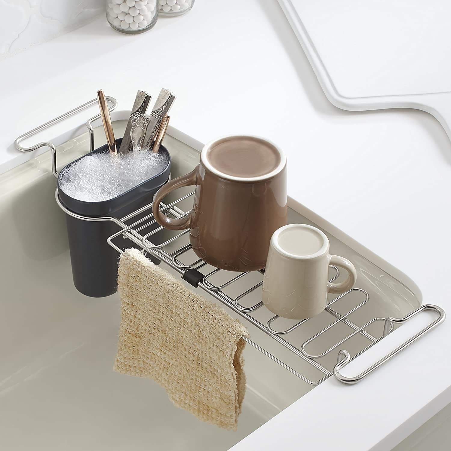 The extendable caddy placed inside a sink and loaded with clean mugs, silverware, and a wet dish rag