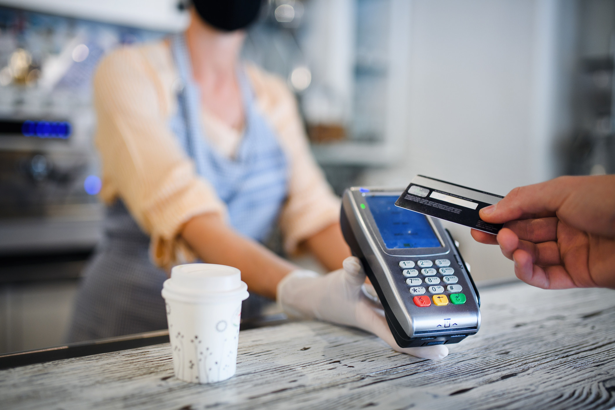 A person paying for coffee with a card