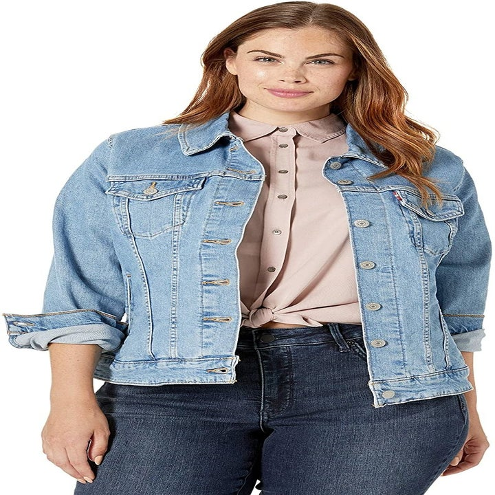 A model wearing the jacket in a light wash
