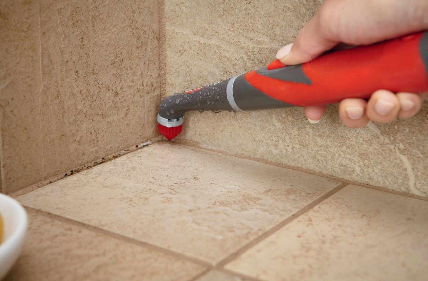 person using red rubbermaid power scrubber to clean up a shower corner