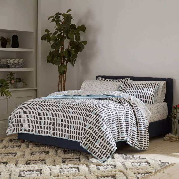a navy blue and turquoise patterned quilt on a bed
