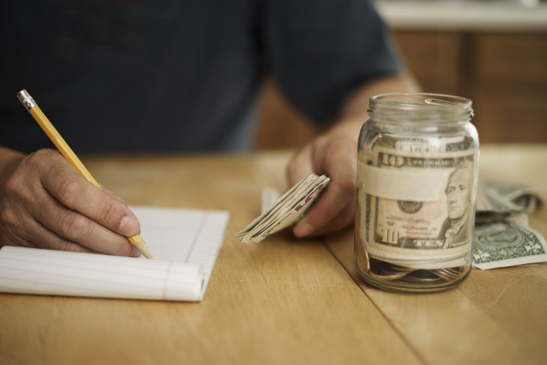 A person holding money and writing on a pad. A jar with cash inside