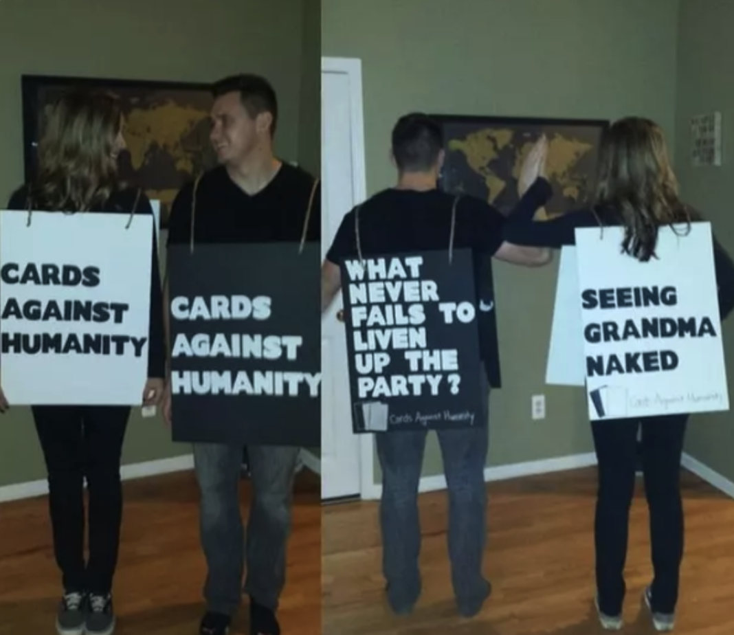 Two people with poster board around their front and back sides with Cards Against Humanity sayings written on them