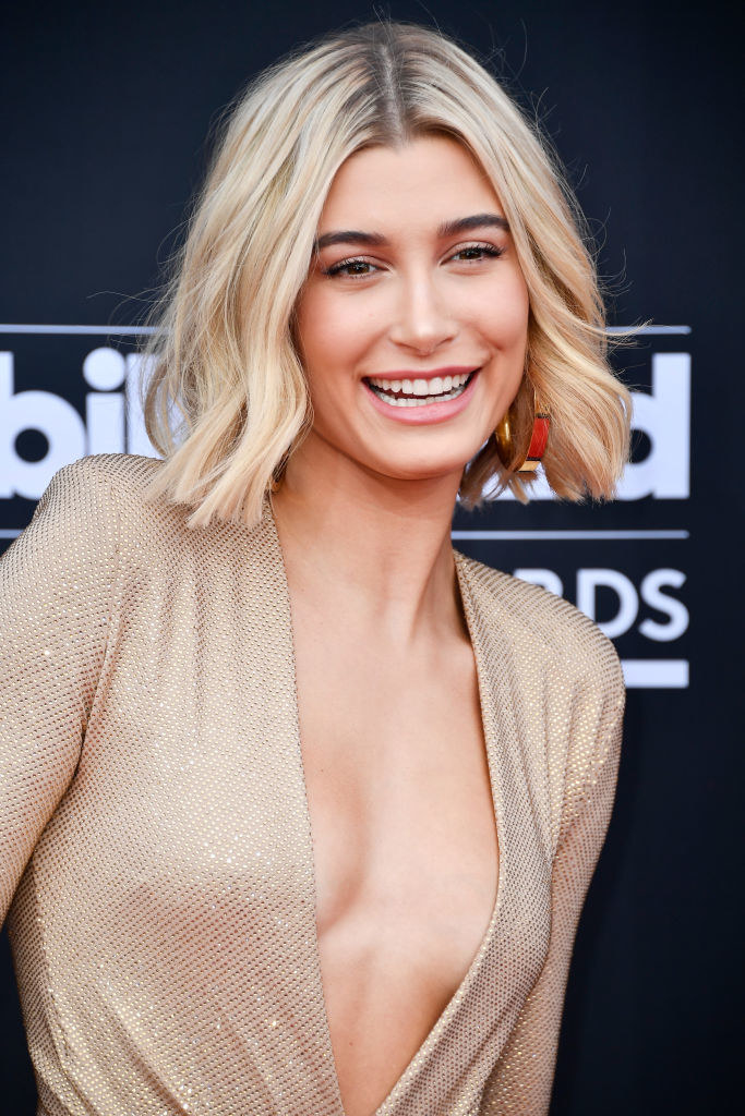 Hailey smiling and wearing a shimmering low cut dress