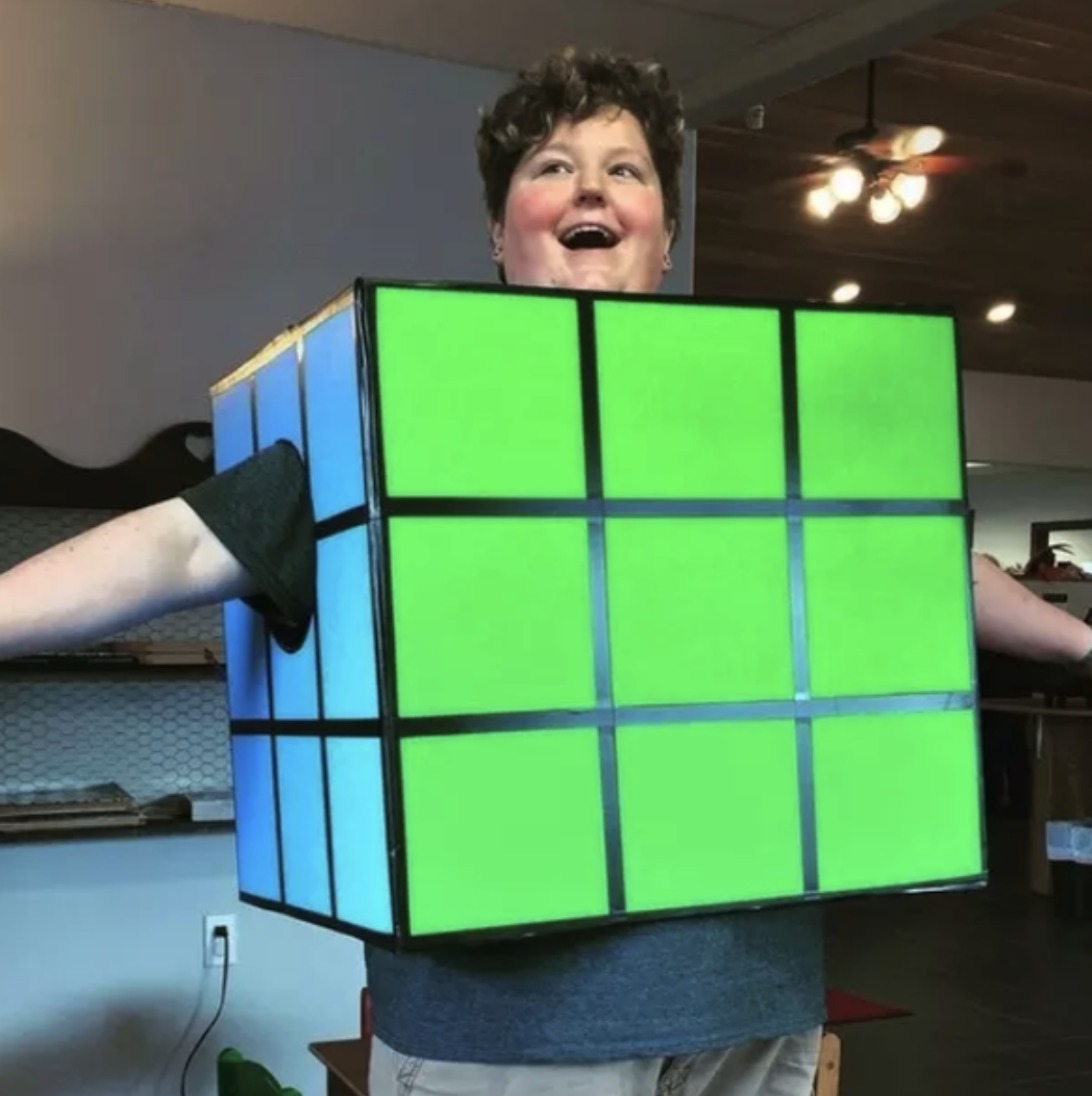 Someone with a box on their body that's made to look like a solved Rubik's Cube