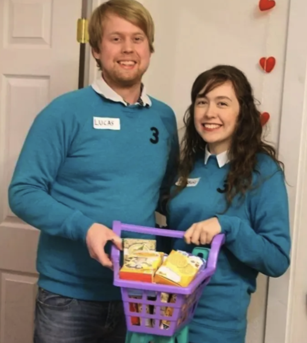 Two contestants wearing traditional blue sweaters, name tags, and the number three, all while holding onto a shopping cart