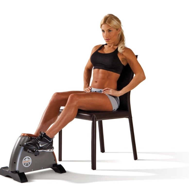 Blonde woman in black sports bra and gray shorts on black chair using mini cycling machine in front of her