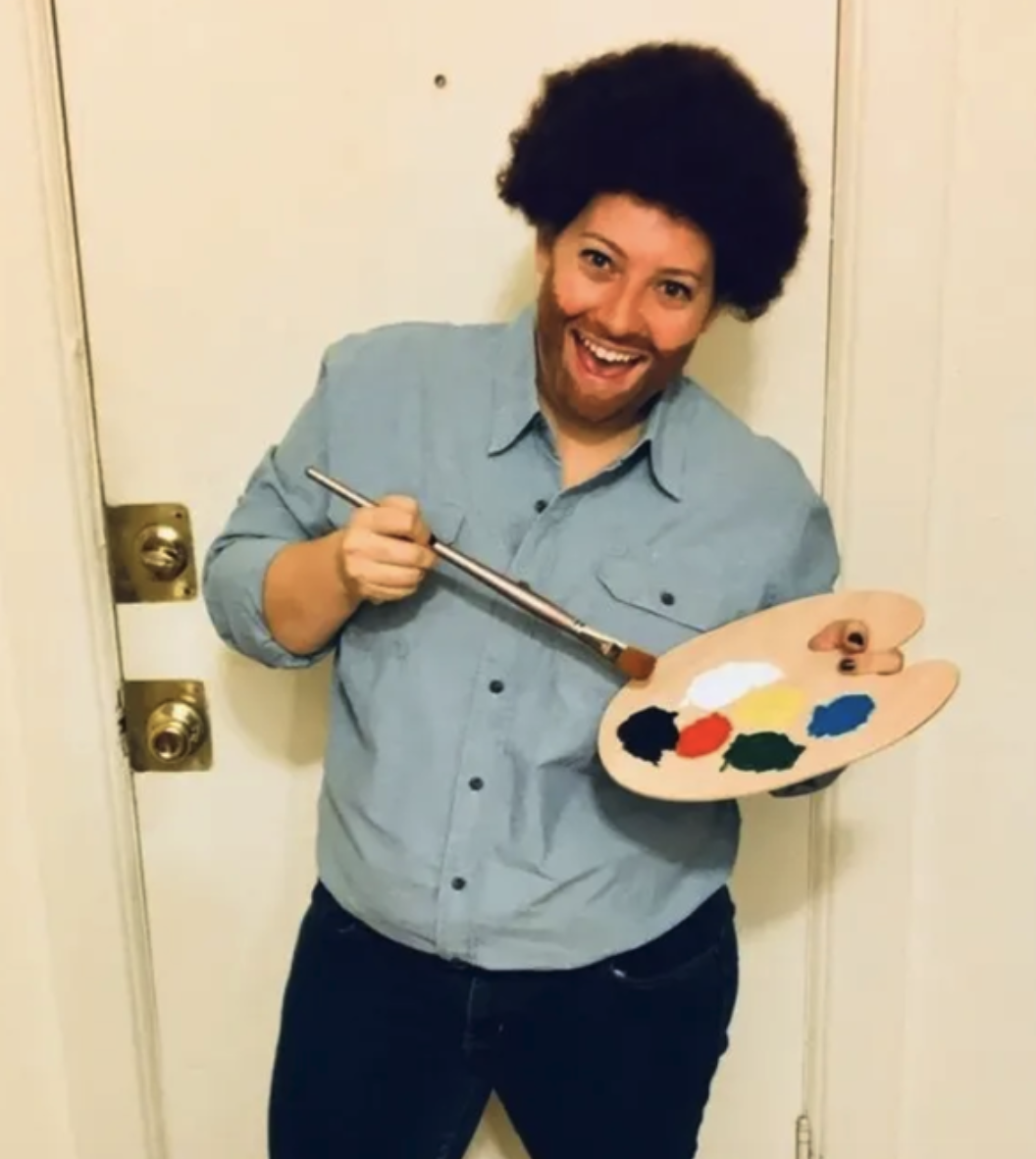 Someone with an afro, beard, and blue dress shit while holding a painting easel