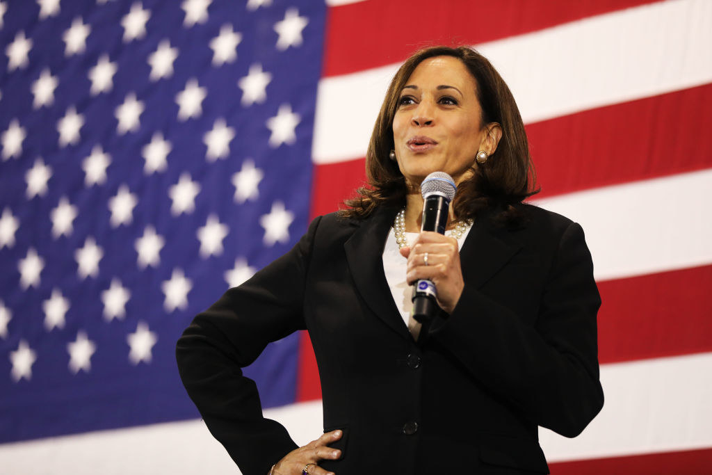 Kamala Harris holding a mic in front of an American flag