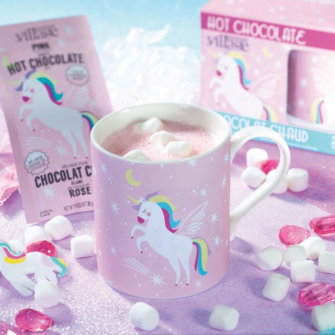A mug filled with unicorn hot chocolate surrounded by marshmallows