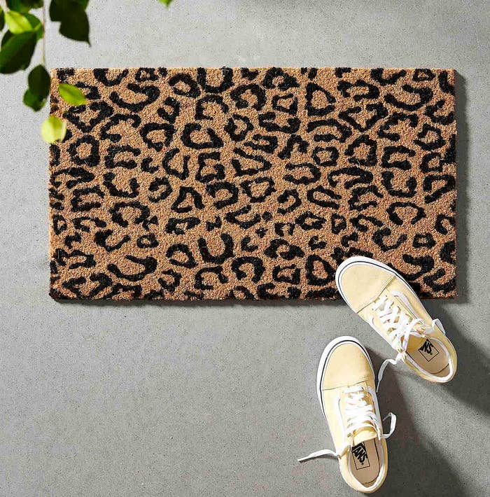 A pair of Vans sneakers on the leopard print mat