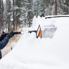 Model using the brush to clear a snowy windshield