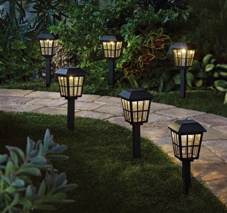 Six black windowed lawn lamps in grass along stone walkway