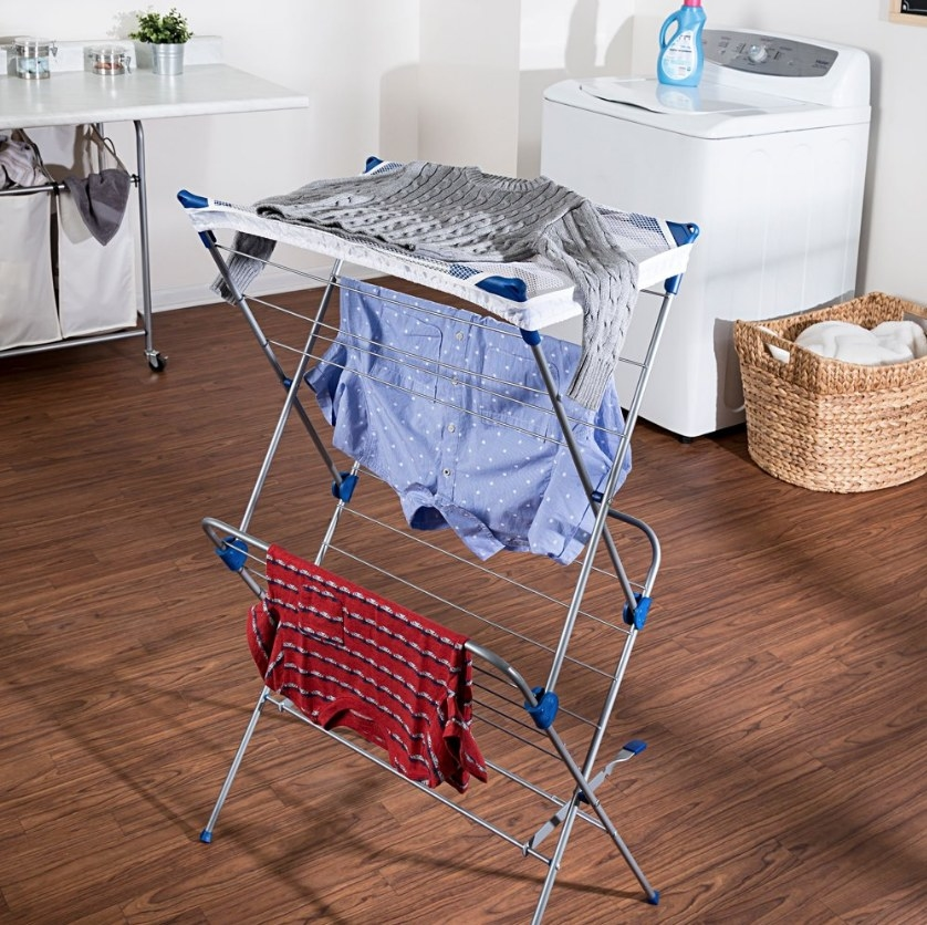 Drying rack with red shirt, blue shirt and gray sweater in laundry room with wood floor