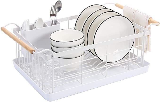 The white dish rack filled with bowls, plates, and utensils