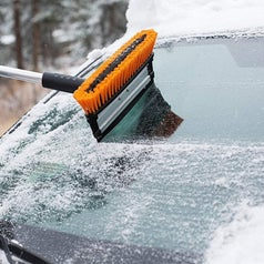 Model using the ice scraper to clear the back windshield of a car