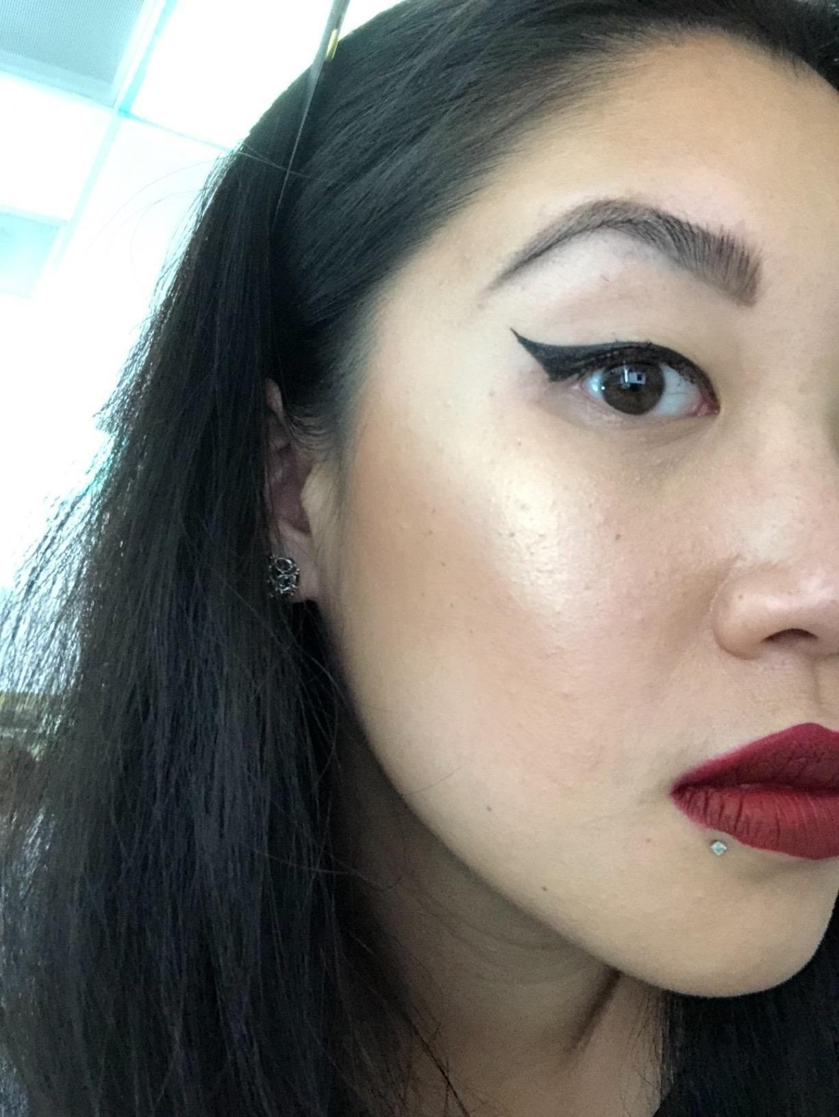 A customer with a full face of makeup and a perfect winged eyeliner using the LA PURE eyeliner