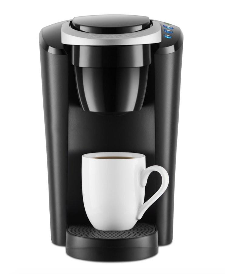 Black Keurig machine with white coffee mug