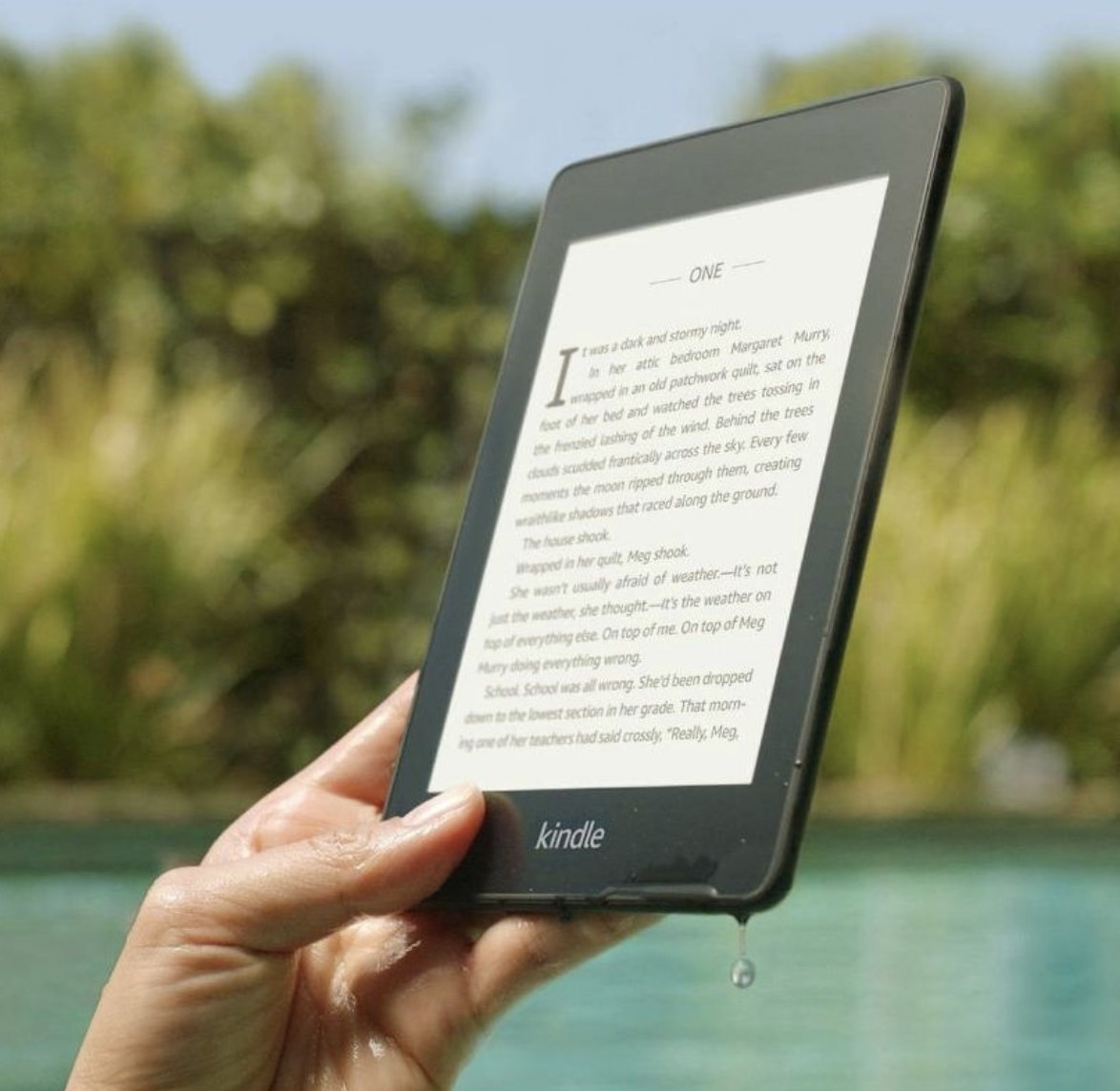 a person holding a kindle in a pool