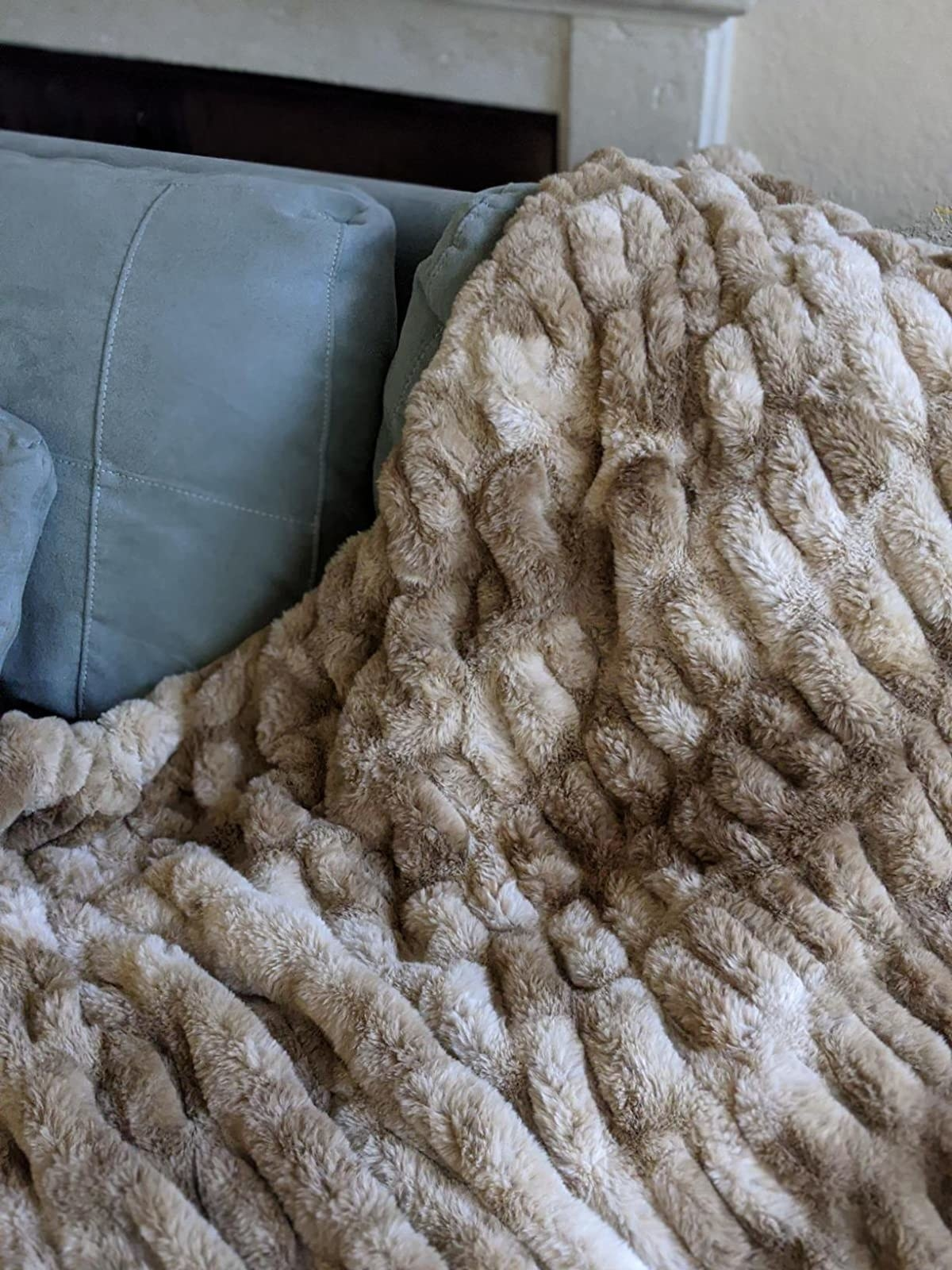 A close up of the beige Chanasya Ruched Royal Faux Fur Throw Blanket on a customer's couch