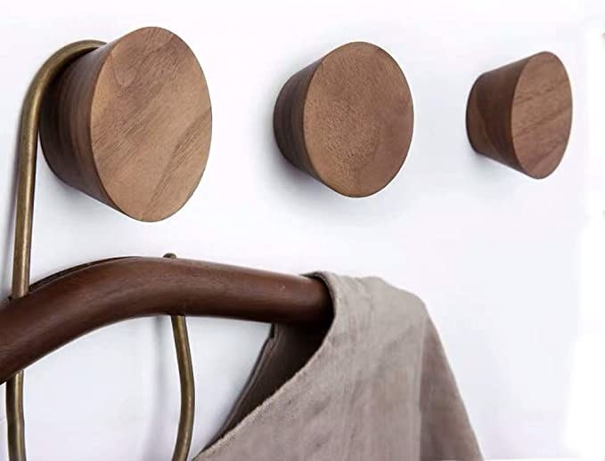 Three circular hooks; one with a clothing hanger