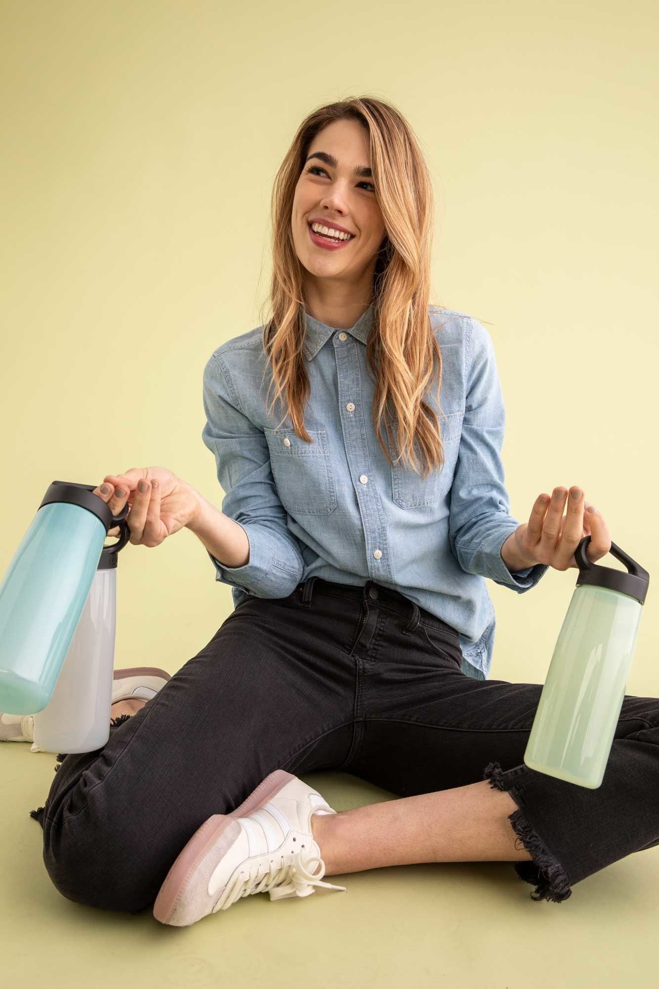 Model holding three different colored water bottles
