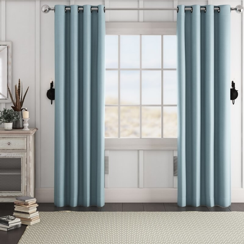 The floor-length curtains in light blue, in two panels, with grommets for hanging