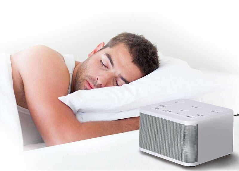 The noise machine, which is compact and rectangular, with setting buttons on top