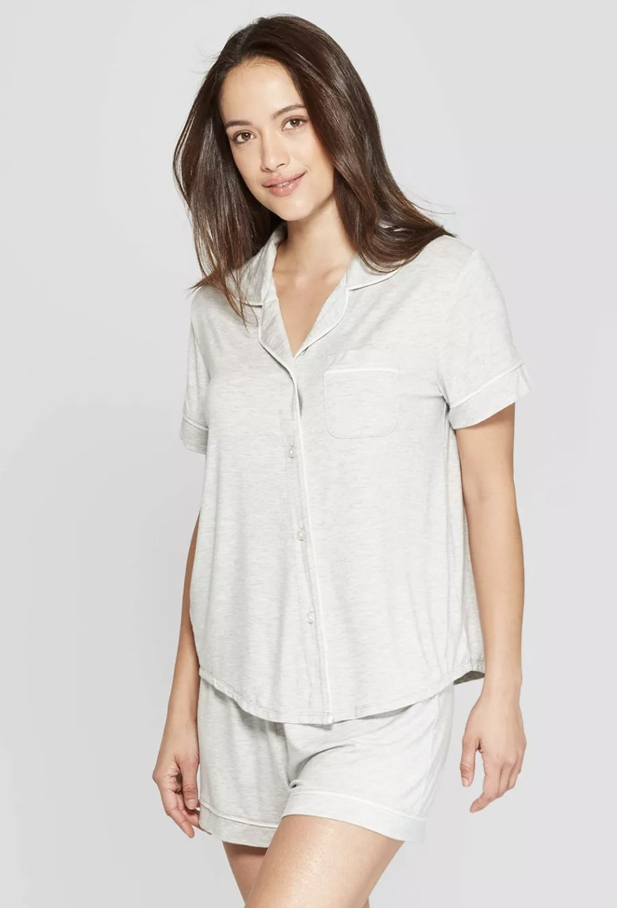 a model in a heather grey pajama set with pajama shorts and a short sleeve button up