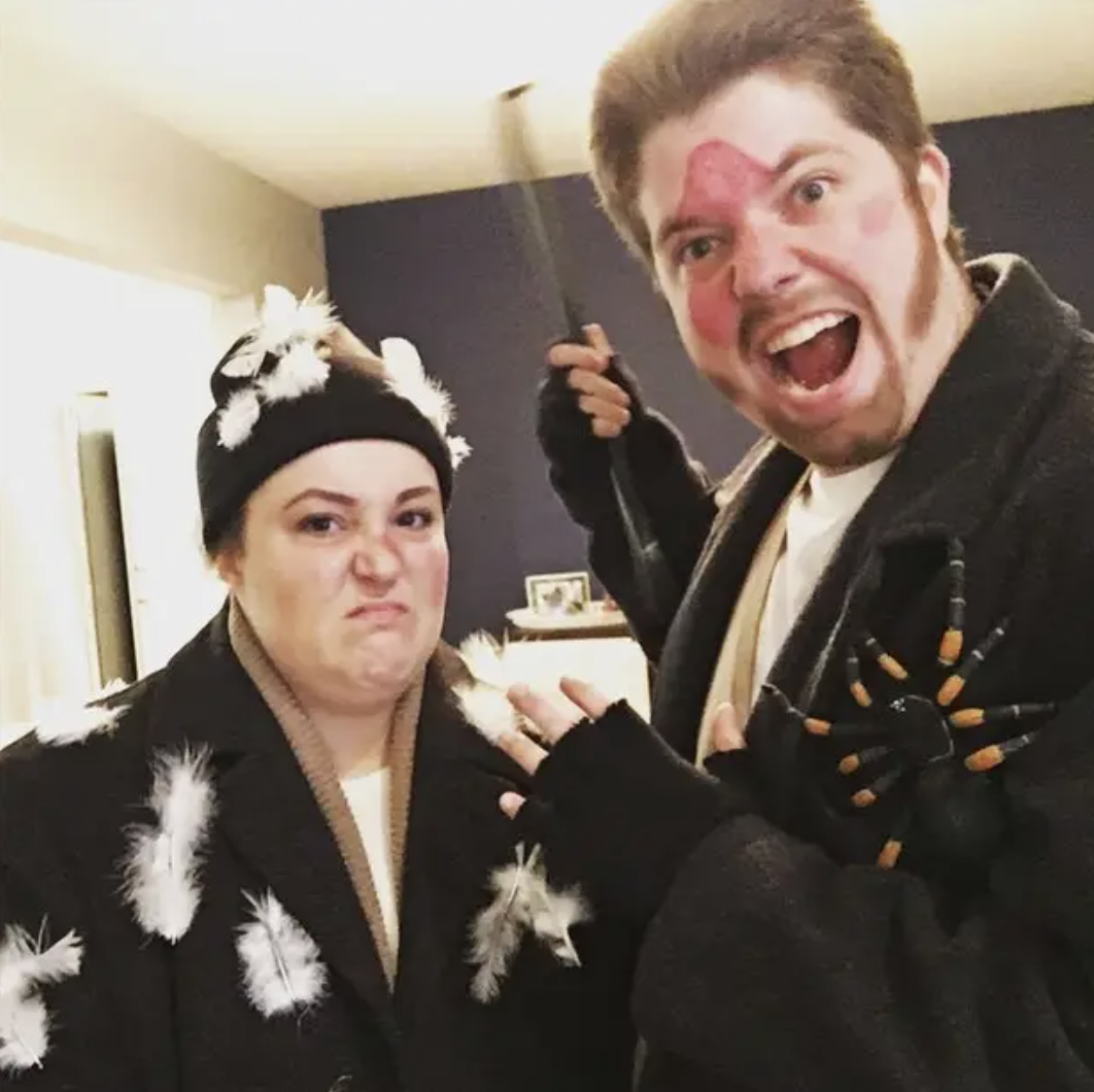 "Two people dressed as the Wet Bandits from ""Home Alone,"" with a fake spider, pillow feathers, and an iron-to-the-face mark on their bodies"