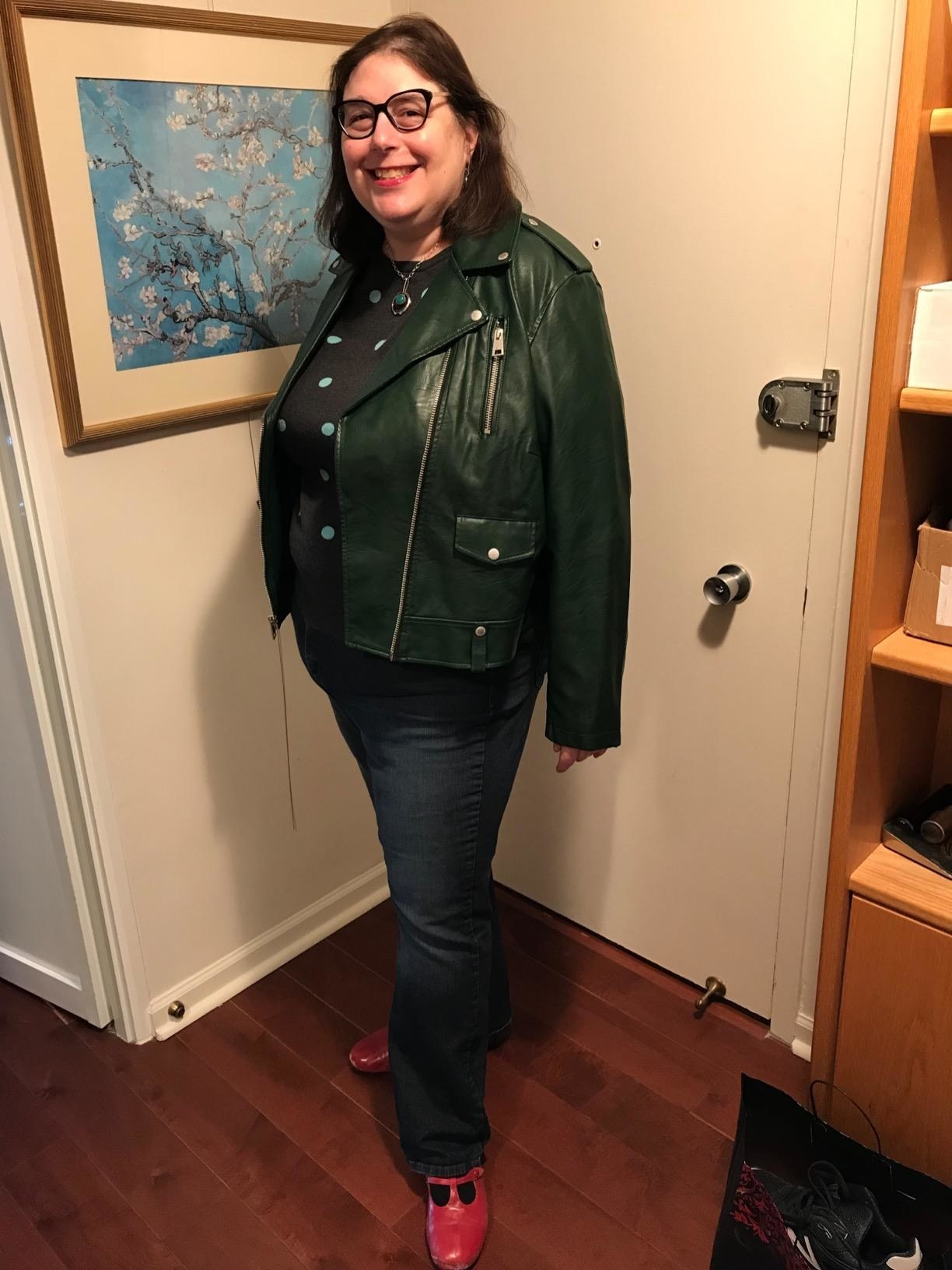 A reviewer wearing the jacket in dark green
