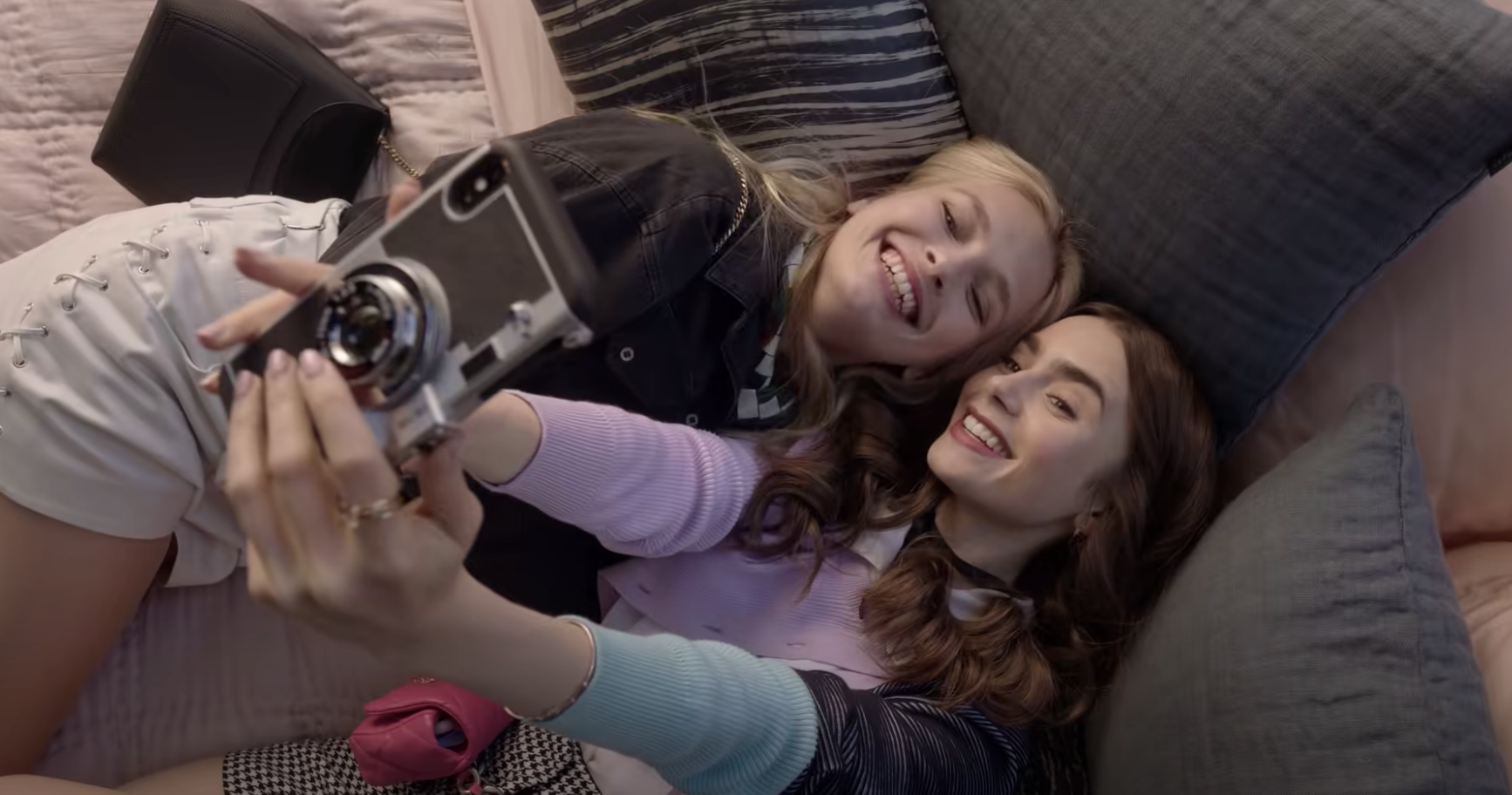 "Emily and Camille smiling for the camera in a bed in ""Emily in Paris"""