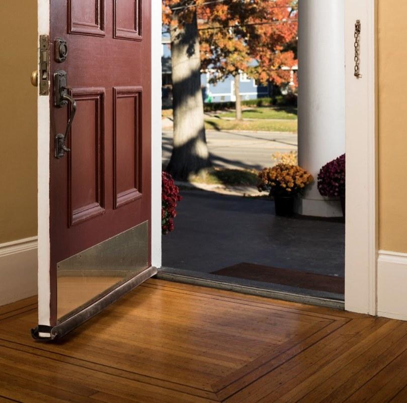 Brown draft door stopper on opened maroon colored, front door