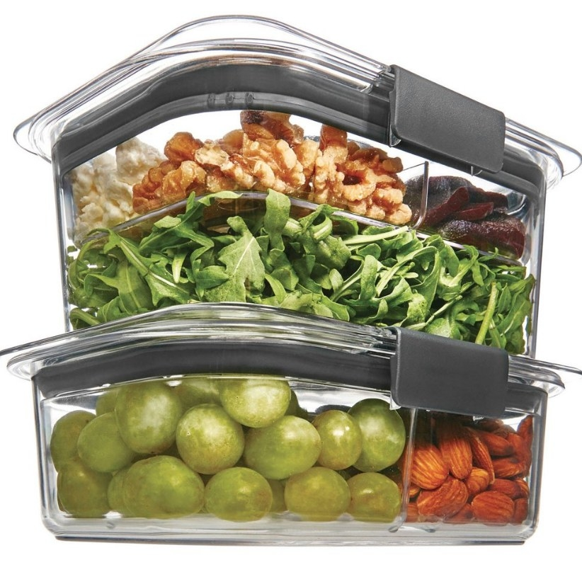 Clear container with gray lid filled with nuts, beets and salad on top of smaller container with grapes and nuts