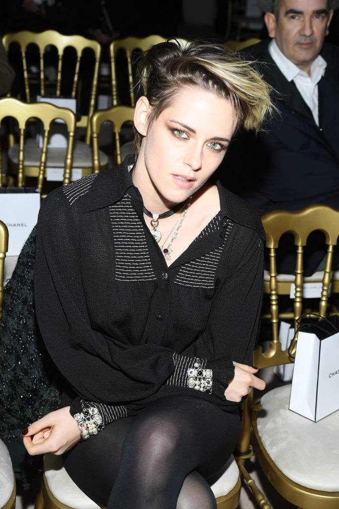 Kristen with dramatic makeup and a button-up dress over tights
