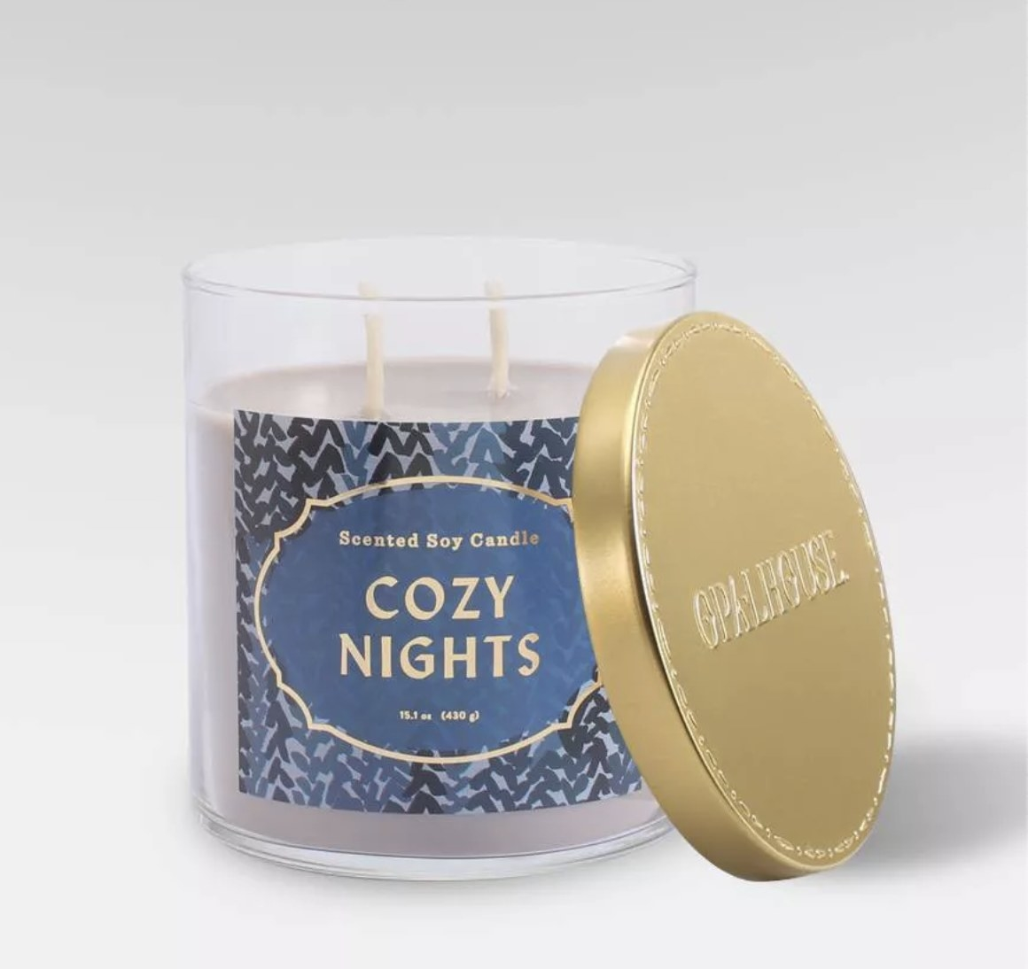 a lilac candle with a gold lid and two wicks. a navy and gold label on the glass jar