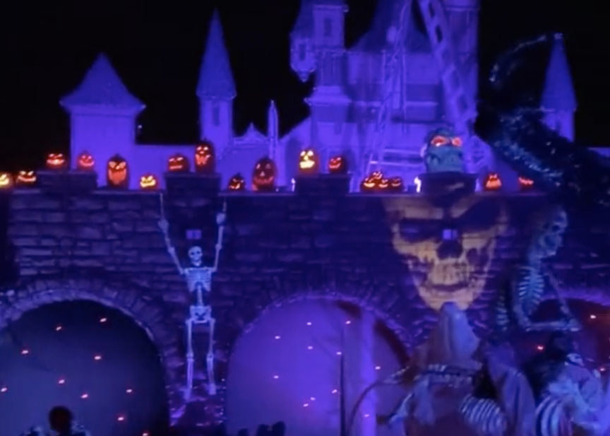 A castle illuminated with purple lights at night featuring skeletons and jack-o-lanterns