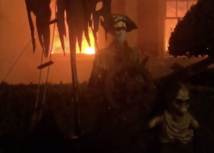 A house that appears to be on fire with a pirate skeleton in the foreground