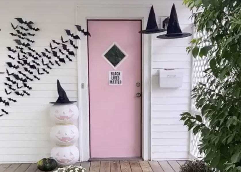 A home with a pink door with white and pink pumpkins outside and bat decorations
