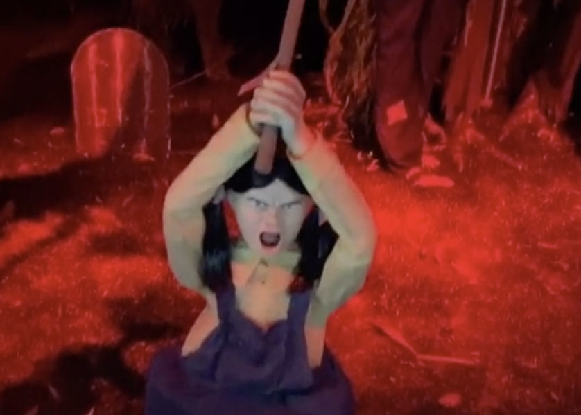 A creepy doll holds an axe in front of a graveyard scene