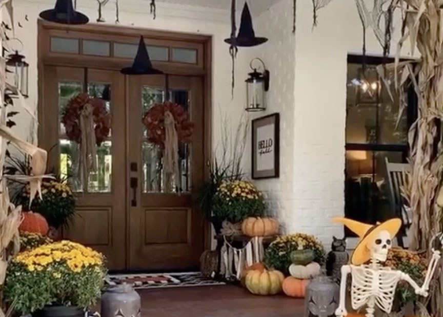 A stunning home with a porch full of yellow and red plants, pumpkins and a skeleton